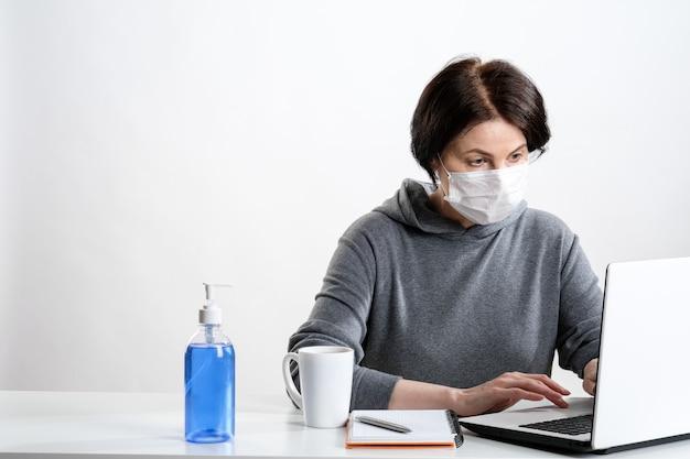 Eine ältere frau in einer schutzmaske arbeitet an einem computer