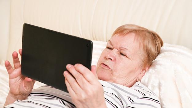 Eine ältere frau liegt mit einem telefon in den händen im schlafzimmer.