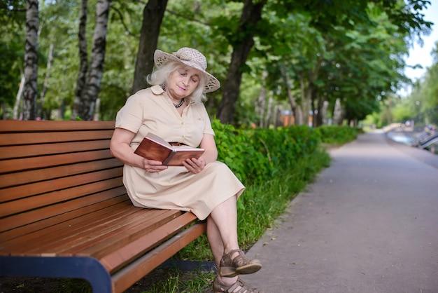 Eine ältere frau liest ein buch im park