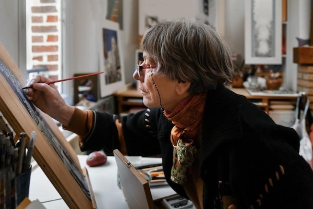 Eine ältere frau malt eine französische gotische kathedrale