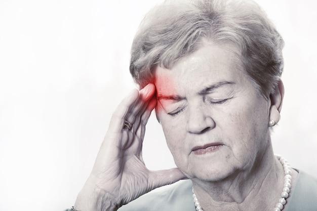 Eine ältere frau mit kopfschmerzen