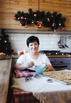 Eine ältere frau zu hause in der küche, die weihnachtsleckereien vorbereitet. familien tradition.