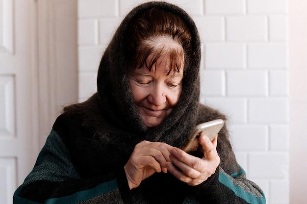 Eine ältere großmutter hält zum ersten mal ein handy in der hand