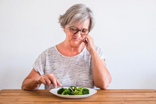 Eine ältere und reife frau, die eine diät macht und gesund isst und mit ekelgesicht auf den brokkoli auf dem holztisch schaut