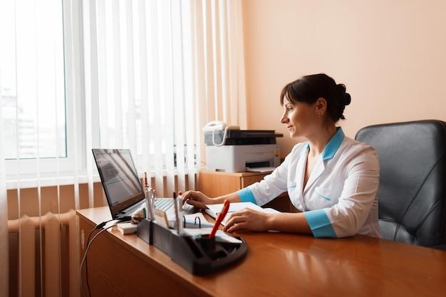 Eine ärztin im weißen bademantel arbeitet hinter einem laptop in der nähe eines fensters in einem krankenhaus. verantwortungsvolle arbeit.