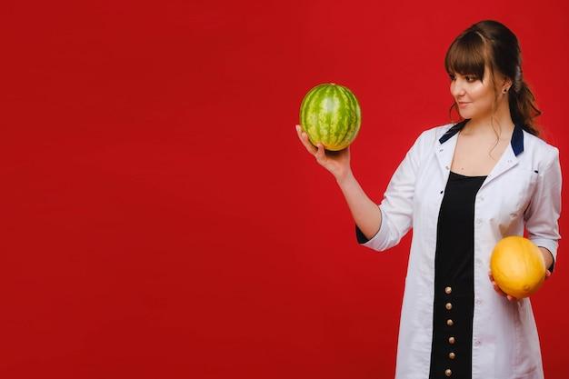 Eine ärztin in einem weißen kittel mit früchten in den händen posiert auf einem roten