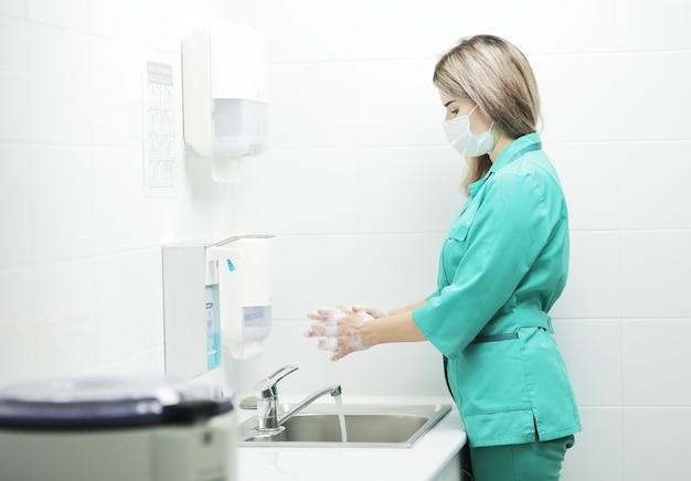 Eine ärztin in schutzmaske und medizinischer uniform wäscht sich die hände