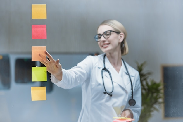 Eine ärztin klebt aufkleber auf ein transparentes glas, um einen strategischen plan zu entwickeln.