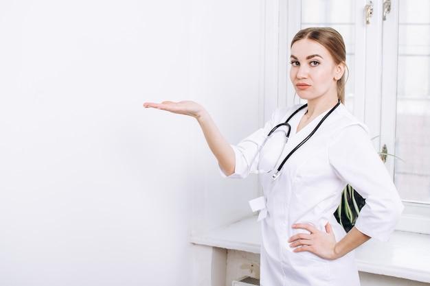 Eine ärztin mit einem stethoskop in einem weißen kittel steht auf einer weißen wand