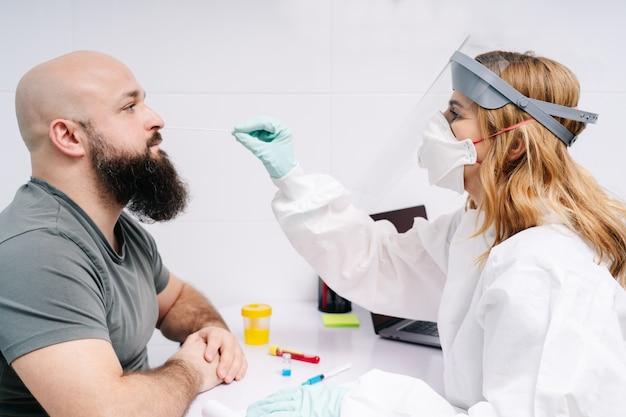 Eine ärztin testet eine patientin mit einem wattestäbchen in einem krankenhauslabor