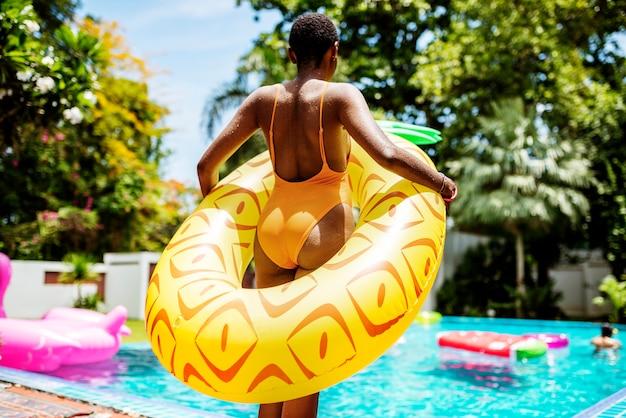 Eine afrikanische frau, die das pool mit einem aufblasbaren floss bereitsteht und die sommerzeit genießt