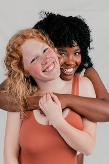 Eine afrikanische junge frau, die ihre kaukasische freundin von hinten umfasst