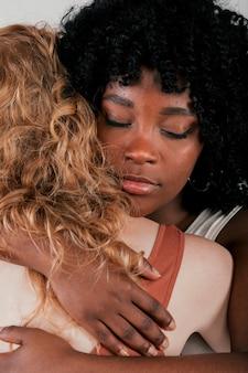 Eine afrikanische junge frau, die kaukasische frau umarmt
