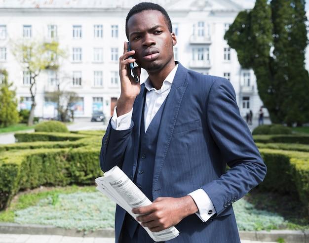 Eine afrikanische junge geschäftsfrau, welche die zeitung in der hand spricht auf smartphone hält