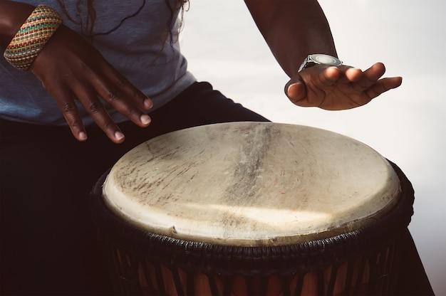Eine afrikanische musikerin spielt die djembe-trommel. sie ist vor einem weißen hintergrund.