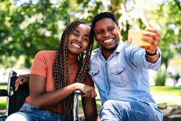 Eine afroamerikanerin im rollstuhl, die ein selfie mit ihrem freund nimmt, während sie einen tag im park zusammen genießt