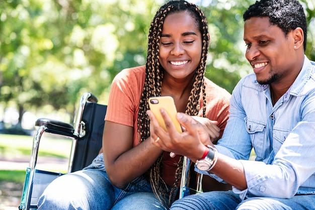 Eine afroamerikanerin im rollstuhl, die mit ihrem freund ein mobiltelefon benutzt, während sie gemeinsam einen tag im park genießt.
