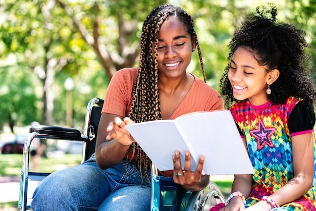 Eine afroamerikanerin im rollstuhl, die mit ihrer tochter einen tag im park genießt, während sie zusammen ein buch liest.