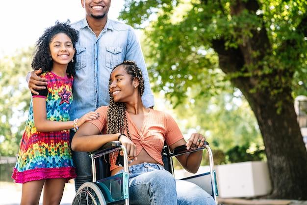 Eine afroamerikanerin im rollstuhl, die mit ihrer tochter und ihrem ehemann einen spaziergang im freien genießt.