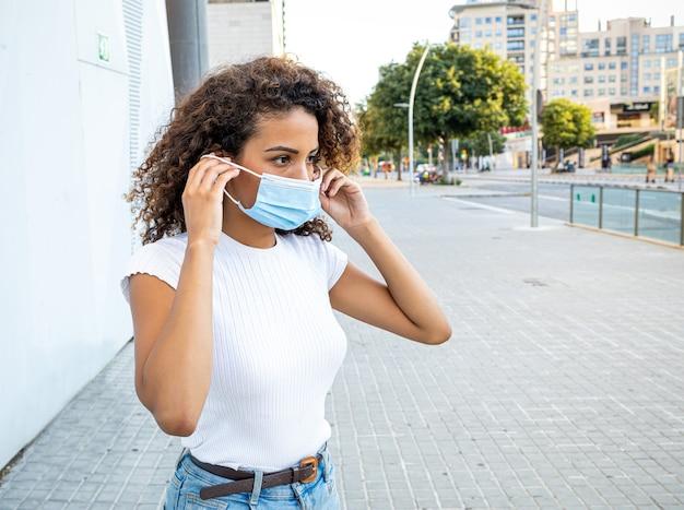 Eine afroamerikanische frau, die eine gesichtsmaske anzieht