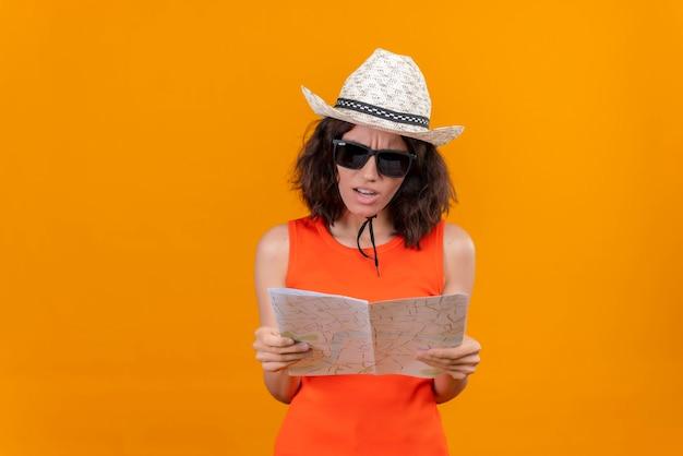 Eine aggressive und verärgerte junge frau mit kurzen haaren in einem orangefarbenen hemd, das sonnenhut und sonnenbrille trägt, die karte betrachten