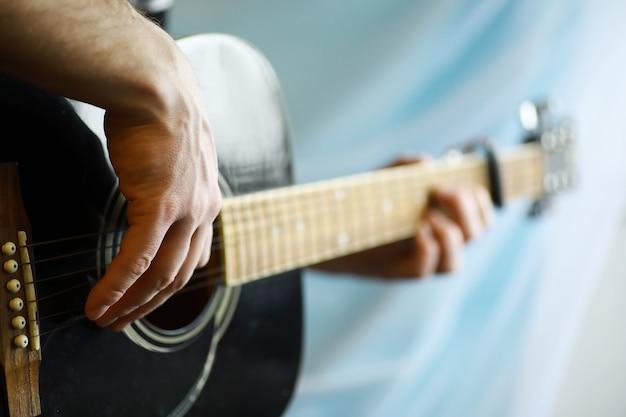 Eine akustikgitarre für einen künstler, der auf der bühne ein saitenmusikinstrument spielt. schwarze gitarre mit kapodaster. musikalischer hintergrund.