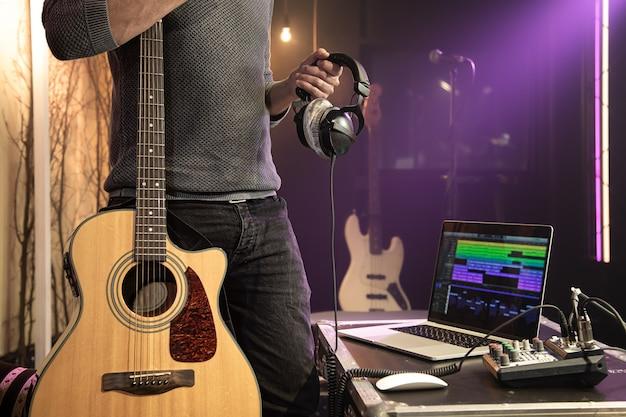 Eine akustikgitarre und professionelle kopfhörer in den händen eines mannes in einem aufnahmestudio an einer verschwommenen wand.
