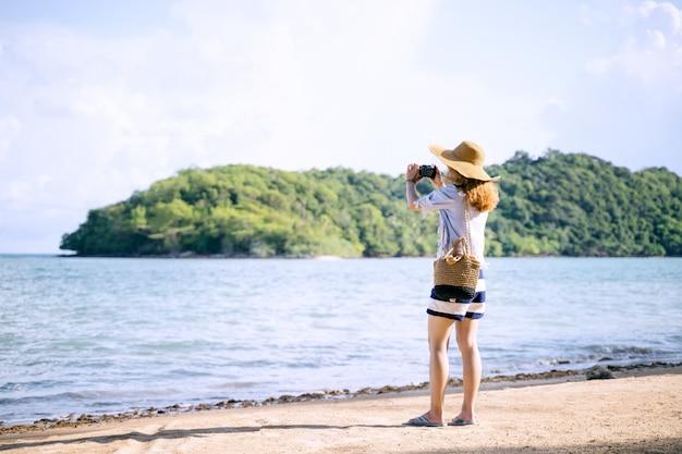 Eine alleinstehende frau, die ein foto auf dem strand, koh mark thailand macht
