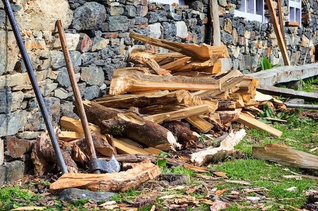 Eine alte hölzerne axt nahe steinmauer vor dem hintergrund des gehackten brennholzes. nepal