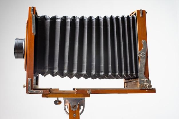 Eine alte holzkamera des letzten jahrhunderts mit einem akkordeon.