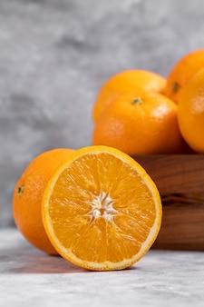 Eine alte holzkiste voller ganzer und geschnittener orangenfrüchte auf marmor