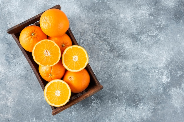 Eine alte holzkiste voller geschnittener und ganzer saftiger orangenfrüchte.