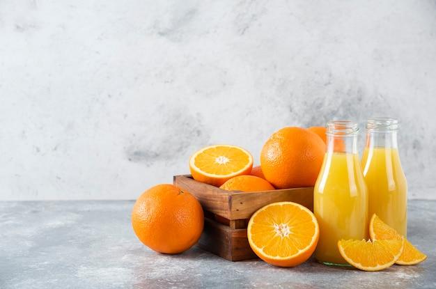 Eine alte holzkiste voller saftiger orangenfrüchte auf steintisch.