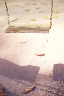 Eine alte holzschaukel hing im park, weiches pastellfarbenes bild.