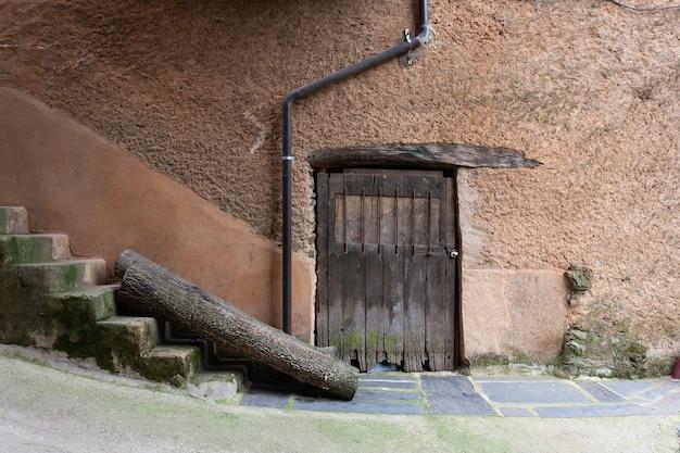 Eine alte holztür mit einem schmiedeeisernen fenster mit einem holzsturz in einem terrakottafarbenen lehmziegel