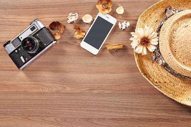 Eine alte kamera, die auf einem holztisch neben der draufsicht des smartphones und des strohhutes liegt