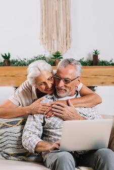 Eine ältere Frau, die ihren Ehemann unter Verwendung des Laptops umfasst