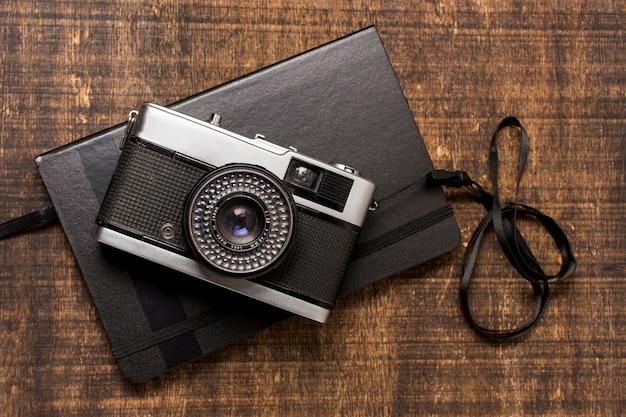 Eine altmodische kamera über dem geschlossenen tagebuch auf hölzernem schreibtisch