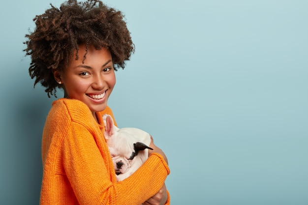 Eine amerikanische amerikanerin, die einen orangefarbenen pullover hält, der hund hält