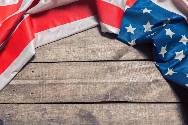 Eine amerikanische flagge, die auf einem gealterten, verwitterten rustikalen hölzernen liegt