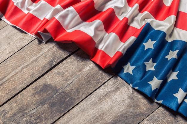 Eine amerikanische flagge, die auf einem gealterten, verwitterten rustikalen holz liegt
