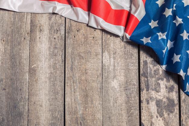 Eine amerikanische flagge, die auf rustikalem hölzernem hintergrund liegt
