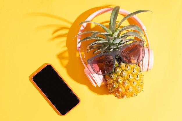 Eine ananas mit einem rosa headset neben einem telefon auf gelbem sommerhintergrund summer