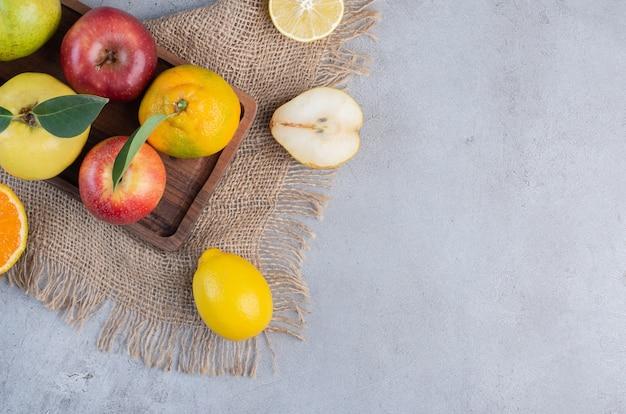 Eine anordnung verschiedener früchte auf einem holzbrett und einem stück stoff auf marmorhintergrund.