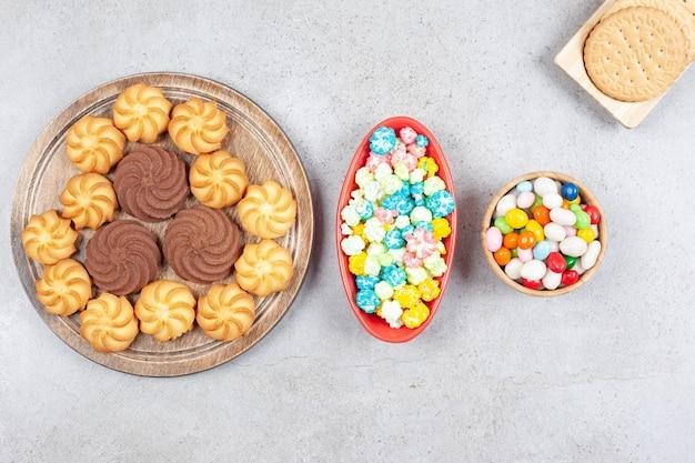 Eine anordnung von keksen, keksen und verschiedenen arten von süßigkeiten auf marmoroberfläche