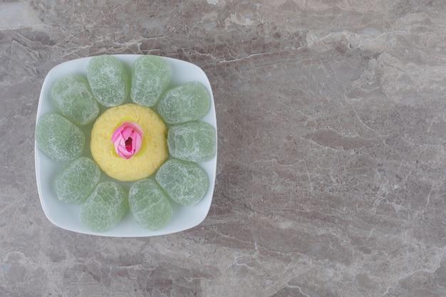 Eine anordnung von marmeladen, einem keks und einer blumenkrone auf einer platte auf marmor