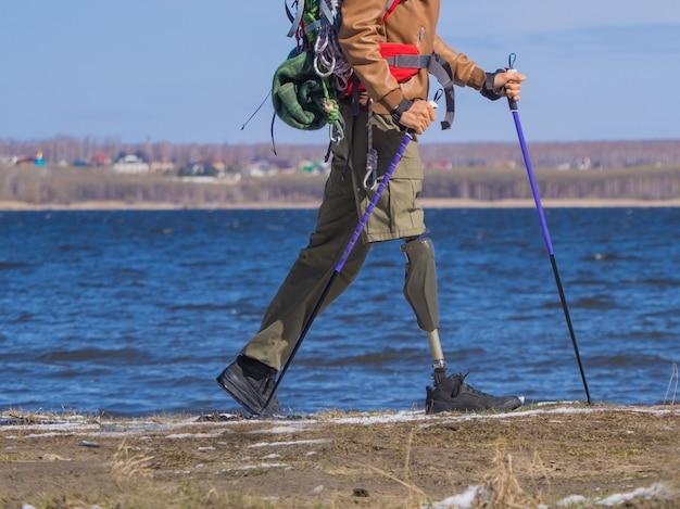 Eine ansicht der beine eines laufenden touristen mit einer beinprothese.
