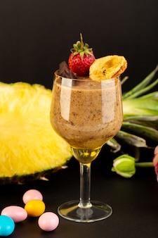 Eine ansicht des braunen schoko-desserts der vorderansicht leckeres köstliches süßes mit schokoladenpulver-schokoriegel und erdbeere mit geschnittener exotischer ananas auf dem dunklen hintergrund süßes erfrischungsdessert