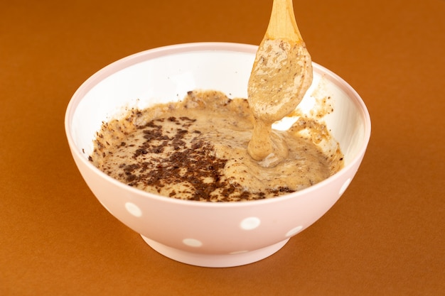 Eine ansicht des braunen schoko-desserts der vorderansicht leckeres leckeres süßes mit pulverisiertem kaffee innerhalb der weißen platte lokalisiert auf dem süßen erfrischungsdessert des milchkaffeehintergrunds