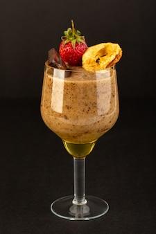 Eine ansicht des braunen schoko-desserts der vorderansicht leckeres leckeres süßes mit schokoladenpulver-schokoriegel und erdbeere auf dem dunklen hintergrund süßes erfrischungsdessert
